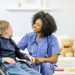 A boy using a wheelchair is being comforted by a friendly-looking nurse.